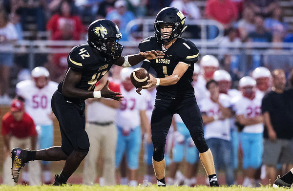 Neosho's quarterback Gage Kelley hands the ball behind the line of scrimmage to Talon Mitchell for a large gain of yards during Friday night's match against Webb City at Neosho High School.<br /> Globe|Israel