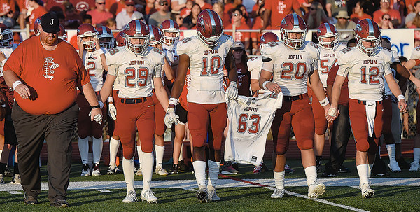 From the left: Joplin coach Curtis Jasper and captains Elijah Eminger, Kaian Roberts Day, Isaiah Davis and Blake Tash walk to midfield with the jersey of Kadin Roberts Day for the pregame coin tosson Saturday night at Webb City.<br /> Globe | Laurie Sisk