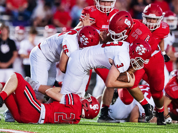 Bulldog's Jaycob Colgin (below) and Alex Harsh (top) tackle Ozark's Chance Strickler (3) during their Homecoming game on Friday evenining at Carl Junction High School.<br /> Globe|Israel Perez