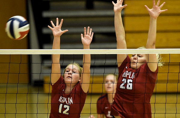 Joplin's Addison Saunders (12) and Anna Neuendorf (26) try to block a spike during a match against Rogers at the Dr. Jeffrey Knutzen CJ Classic on Saturday at Carl Junction High School.<br /> Globe | Laurie Sisk