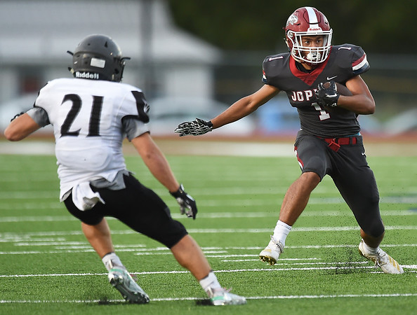 Joplin's Zach Westmoreland (10) looks to get past Willard's Ethan Thompson (21) after a second quarter interception during the Eagles season opener on Friday night at Junge Stadium.<br /> Globe | Laurie Sisk