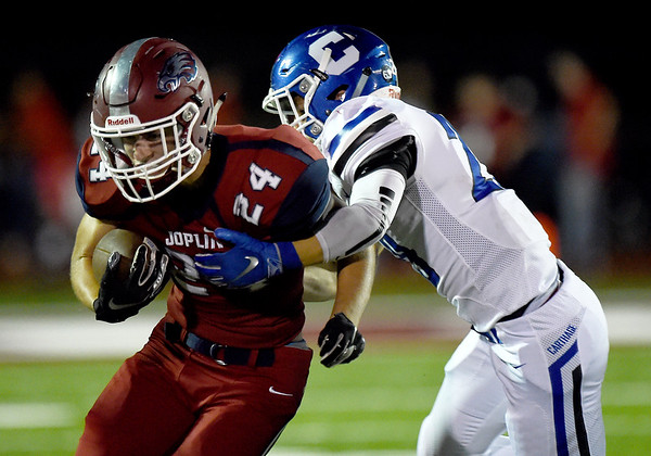 Joplin kick returner Landen Atherton (24) tries to get past Carthage's Sylas Browning (29) during their game on Friday night at Junge Field.<br /> Globe | Laurie Sisk