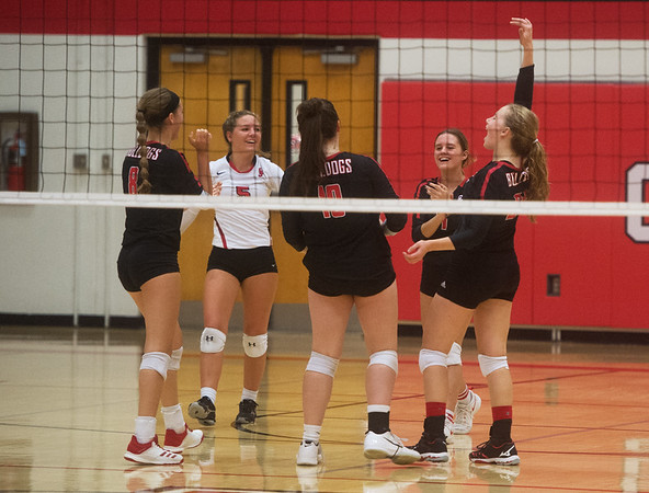 Members of the Carl Junction volleyball team celebrate the winning point against Carthage during Tuesday's match in Carl Junction.<br /> Globe | Roger Nomer
