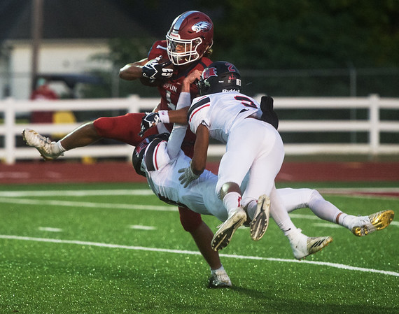 Joplin's Zach Westmoreland secures a catch and pushes away Branson's Ty Werling (7) and D'Shawn Craigg (2) to score a touchdown during Friday's game at Joplin.<br /> Globe | Roger Nomer