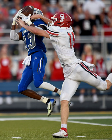 Carthage receiver Marcus Huntley (13) secures a pass despite an interference call on Carl Junction's Garret Taylor (16) during their game on Friday night at Carthage.<br /> Globe   Laurie SIsk