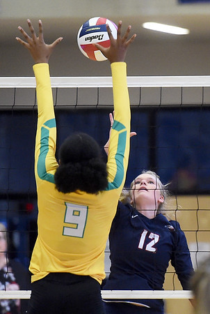 Joplin's Addison Saunders (12) tries to get a spike past Parkview's Mikaela Whalen (9) during their match on Tuesday night at Kaminsky Gymnasium.<br /> Globe | Laurie Sisk
