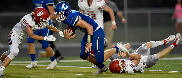 Carthage quarterback Patrick Carlton (17) runs for a first down as Carl Junction's Mylas Derfelt (4) and Garret Taylor (16) defend during their game on Friday night at Carthage.<br /> Globe | Laurie SIsk