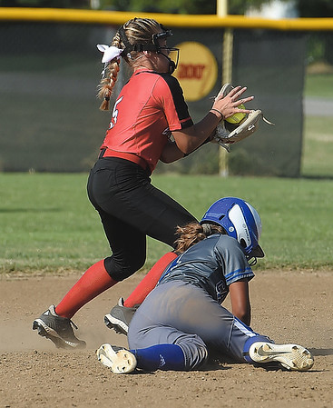 Carthage's Natalie Rodriguez slides back into second base to avoid a double play as Carl Junction's Sammie Sims fields the throw during their game on Tuesday at CJHS.<br /> Globe | Laurie Sisk