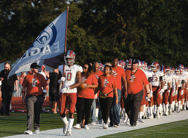 Flanked by family, coaches and teammates, Kaian Roberts Day carries the Joplin High School school flag onto the field before the start of the Eagles game against Webb City on Saturday night at Webb City High School.<br /> Globe | Laurie Sisk