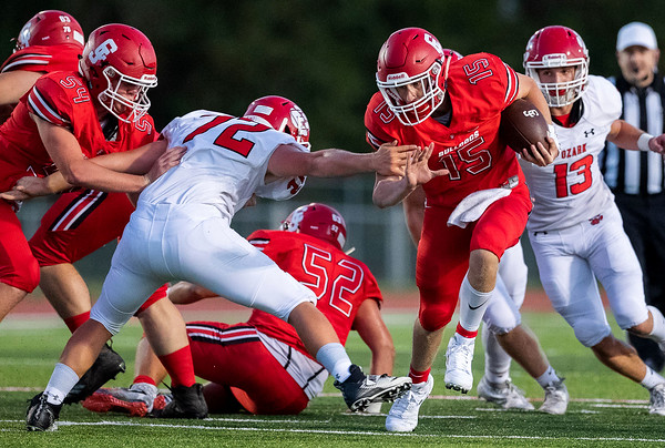 Bulldog's Drew Patterson (15) runs ball as he breaks the tackle of Kaiden Shuler (72) of Ozark during their Homecoming game on Friday evenining at Carl Junction High School.<br /> Globe|Israel Perez