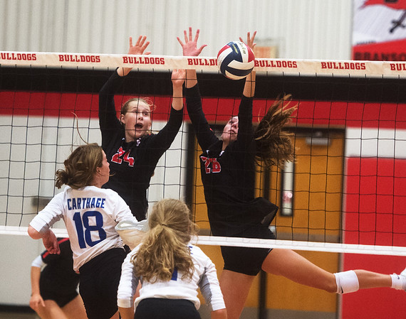 Carl Juntion's Maggie Brown (24) and Salma Lewis (26) team up for a block against Carthage on Tuesday at Carl Junction.<br /> Globe | Roger Nomer