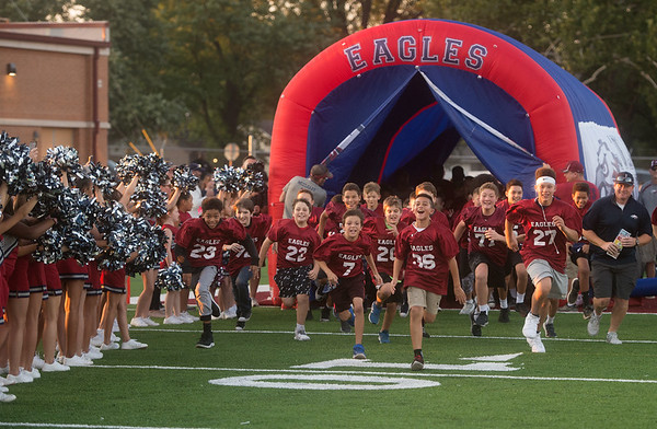 Joplin Youth Football Association sixth graders run onto the field at Junge Stadium as they are introduced before Friday's Joplin High School game against Branson.<br /> Globe | Roger Nomer