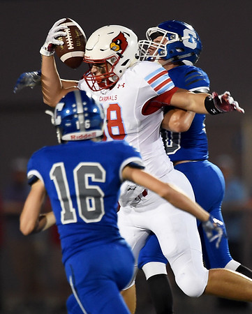 Webb City tight end Gary Clinton (98) uses his helmet to secure a catch as Carthage's Caden Kabance (16) and Justin Sneed (20) defend during their game on Friday night at Carthage High School.<br /> Globe | Laurie Sisk