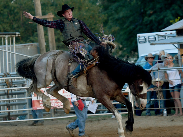 Ken Justeson, of Fort Scott hangs on during the bareback competition on Friday night at the Columbus Saddle Club Rodeo in Columbus.<br /> Globe | Laurie Sisk