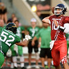 Pittsburg quarterback Chase Curtis passes to a teammate as Grant Fairchild pursues during the first quarter of the Kansas Shrine Bowl on Saturday night at Carnie Smith Stadium.<br /> Globe | Laurie Sisk