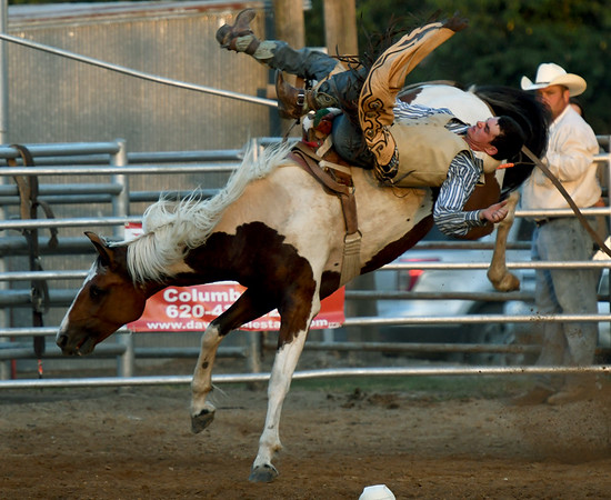 Michael McCammon, of Fort Scott, hangs on during the bareback competition on Friday night at the Columbus Saddle Club Rodeo in Columbus.<br /> Globe   Laurie Sisk