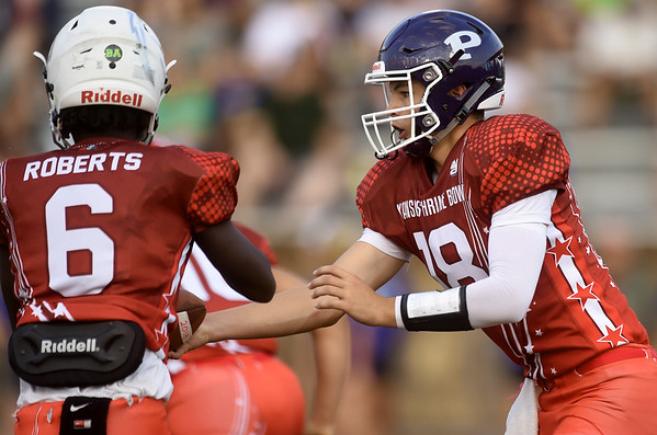 Pittsburg quarterback Chase Curtis hands off to running back Nijel Roberts during the Kansas Shrine Bowl on Saturday night at Carnie Smith Stadium.<br /> Globe   Laurie Sisk