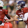 Pittsburg quarterback Chase Curtis hands off to running back Nijel Roberts during the Kansas Shrine Bowl on Saturday night at Carnie Smith Stadium.<br /> Globe | Laurie Sisk
