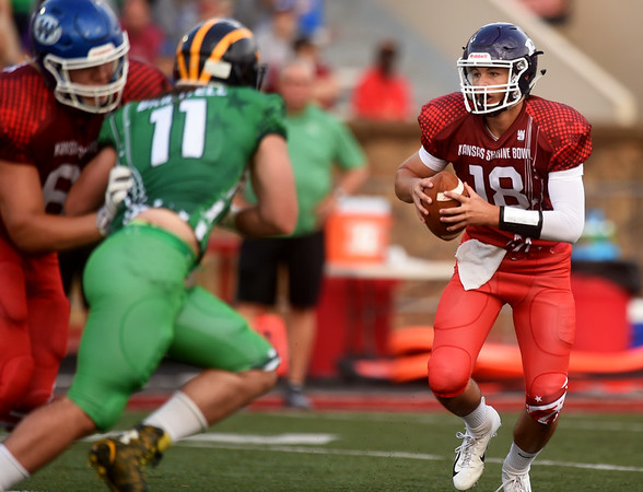 Pittsburg quarterback Chase Curtis looks for room to run as Garrett Bridwell pursues during the first quarter of the Kansas Shrine Bowl on Saturday night at Carnie Smith Stadium.<br /> Globe   Laurie Sisk