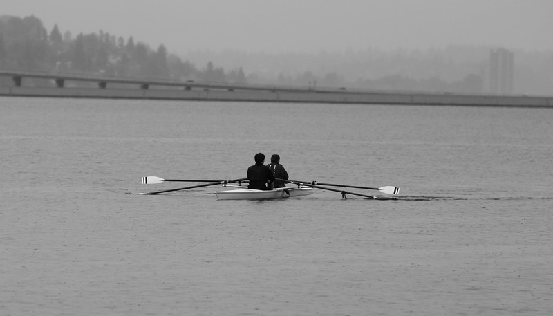 Two men rowing on Lake Washington in Seattle on a rainy day. This photograph is in shades of gray with a bridge and other buildings in the background.