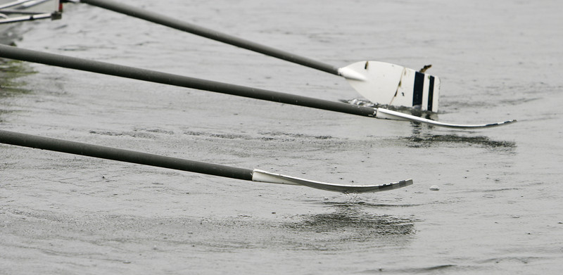 The oars of a novice crew boat are rowing while raindrops splash on the lake. Whether the oars are splashing in unison or this is a chance moment in chaos is an open question...