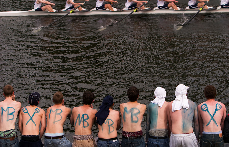 A group of young men rooting and cheering and providing encouragment to their rowing club during a crew race on Opening Day in Seattle. Their backs are painted with the name of their club.