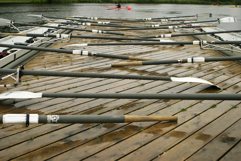 Two racing shells by the dock with oars at rest prior to a rainy practice.