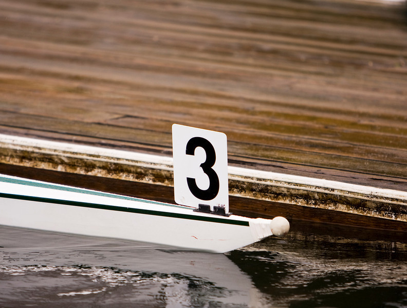 The number three adorns the bow of a racing shell that is about to leave the dock prior to a crew regatta.