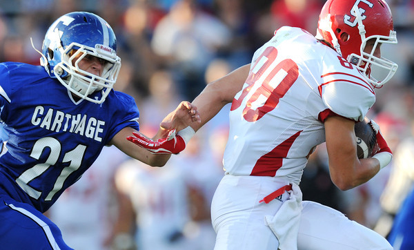 Globe/Roger Nomer<br /> Carl Junction's J Thomas bats away the hand of Carthage's Alex Kennedy during Thursday's game in Carthage.