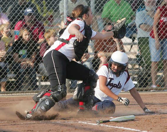 Globe/Roger Nomer<br /> Joplin's Miranda Sanders slides safely into home around Carl Junction's Michaela Horn to score the Eagles' first run of the game during the first game on Tuesday.