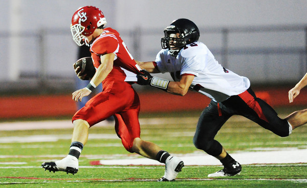 Globe/T. Rob Brown<br /> Lamar's Cedric Gartman grabs hold of Carl Junction runningback Nick Thompson Friday night, Sept. 28, 2012, at Carl Junction's football field.