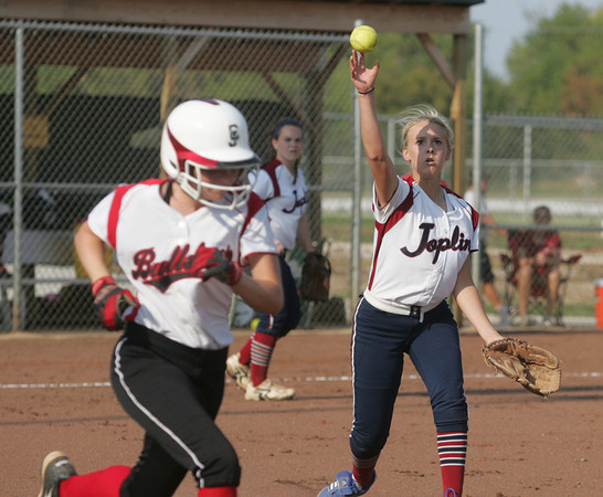 Globe/Roger Nomer<br /> Joplin's Tamarah Mascher throws to first to throw out Carl Juntion's Shelby Sullivan during the first game on Tuesday at the Joplin Athletic Complex.  The tag was fumbled at first, and Sullivan was safe on the play.
