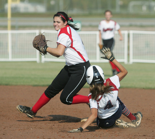 Globe/Roger Nomer<br /> Carl Junction's Tasha Steel sidesteps Joplin's Courtney Shryock as she throws to first on a double play attempt during the first game on Tuesday at the Joplin Athletic Complex.