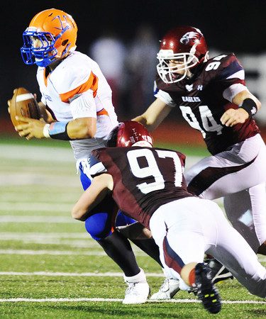 Globe/T. Rob Brown<br /> Joplin's Jarad Bader (97) attempts to sack Hillcrest quarterback Jonah Hill as Joplin's Tucker Wallace (94) moves in to assist during Friday night's game, Sept. 7, 2012, at Joplin's Junge Field.