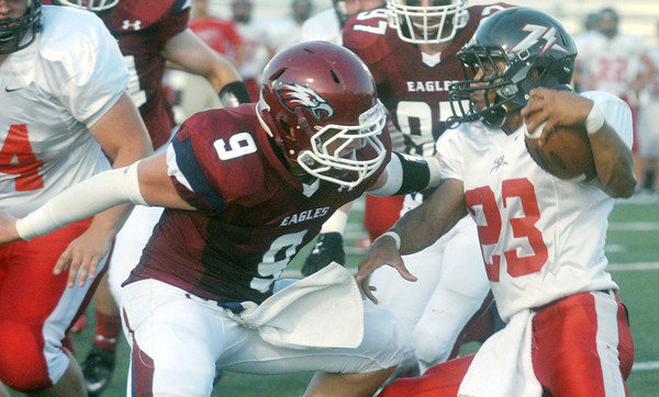 Globe/Roger Nomer<br /> Joplin's Tristan Ash tries to tackle West Plains' Derek Skinner during the first quarter of Friday's game at Junge Stadium.