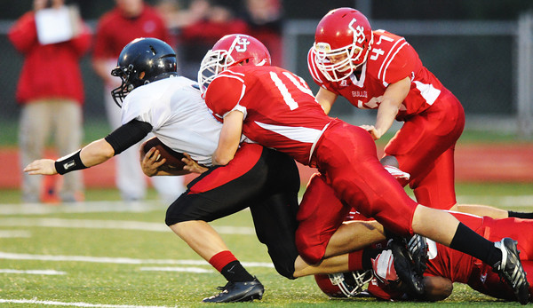 Globe/T. Rob Brown<br /> Carl Junction's Calvin Bremmerkamp (14), with assistance from teammates Tyler Armentrout (47) and Korbyn Carlsen (8), bring down Lamar quarterback Levi Peterson Friday night, Sept. 28, 2012, at Carl Junction's football field.