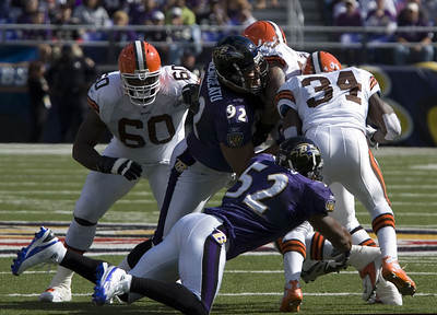 Baltimore linebackers Ray Lewis and Maake Kemoeato try to bring down Cleveland running back Reuben Droughns.