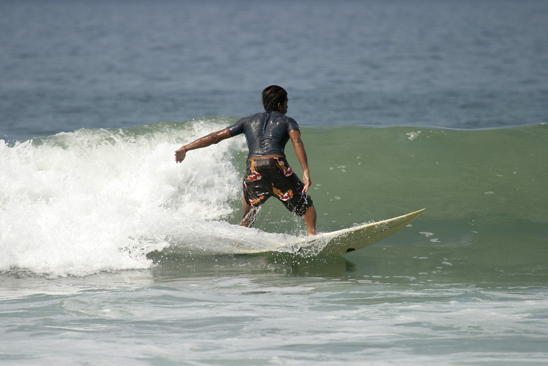 A young man surfing a wave off a beach in Mexico.