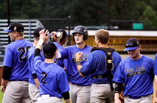 American Legion Post 42's Kyle Beach is congratulated by his teammates after scoring a run during their game against the Hoosier Express, out of Santa Claus, in Floyds Knobs on Tuesday. Staff photo by Christopher Fryer