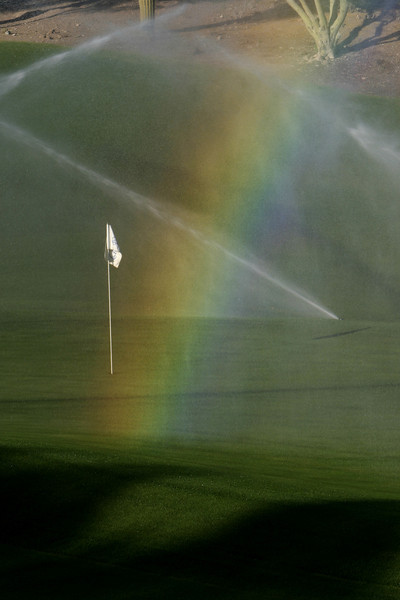 A golf course rainbow resulting from sunlight being diffracted through spray from the sprinkler system. While artificially created, the effect is quite pretty.