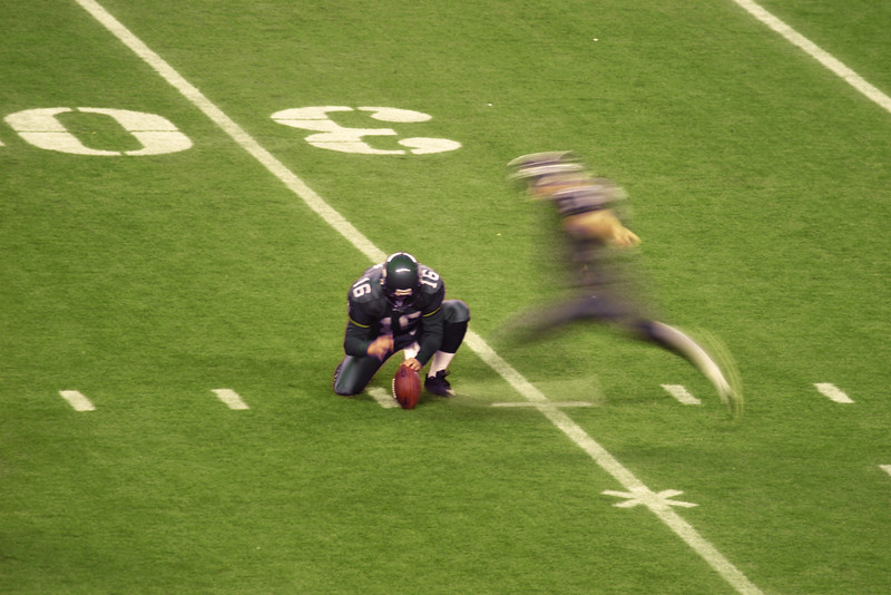 An American high school football kicker attempting a field goal from the thirty yard line. The motion blur of the kicker shows the movement while the holder is almost stationary.
