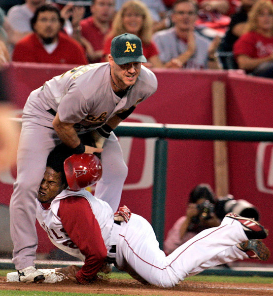 Oakland Athletics third baseman, Jack Hannahan makes the tag on Angels Erick Aybar, in the first inning Monday, at Angel Stadium.