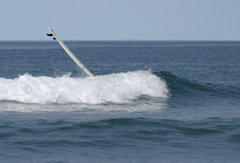 A single surboard is rising above the crest of a wave after the surfer has wiped out.