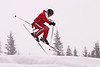 A skier in a red jumpsuit, on a snowy day, about to land a jump after doing some aerials.