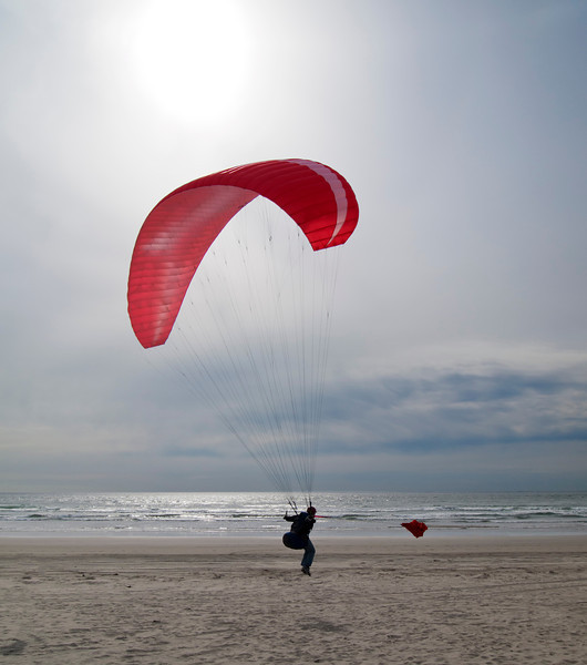 A woman about to take off for a paragliding run over the beaches at Gearhart, Oregon.