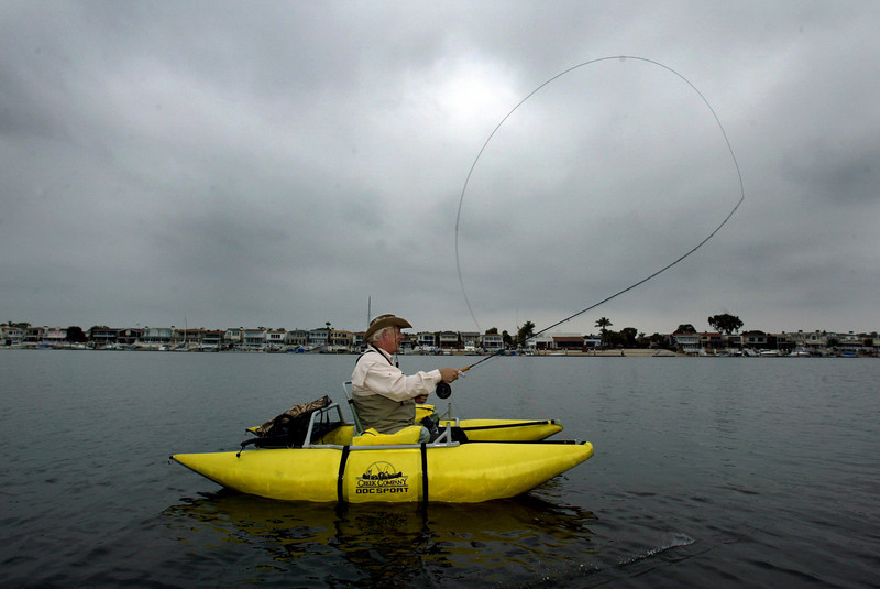 Owner of His and Her Fly Shop in Costa Mesa, Frank Selby, casts his own designed salt water fly from a small pantoon that is used to saltwater fly fish.  He is also the organizer of the 12th annual Father's Day fishing trip.  Each year is a little different route. He is in the Upper Newport Bay where he and 13 others floated and foot paddled over a mile on the ocean for a 4 hour trip.   25 fish were caught and released on the trip including Bass, Spotted Bass and one Halibut.