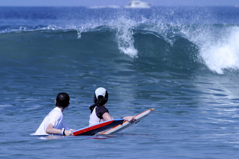 Two children resting on their surfboards as they wait to catch a wave. The wave approaching them is just starting to curl.