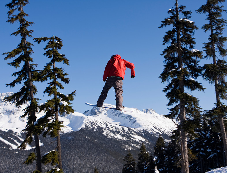 A snowboarder with a bright red coat jumping near Blackcomb Mountain. He is framed by trees on either side.