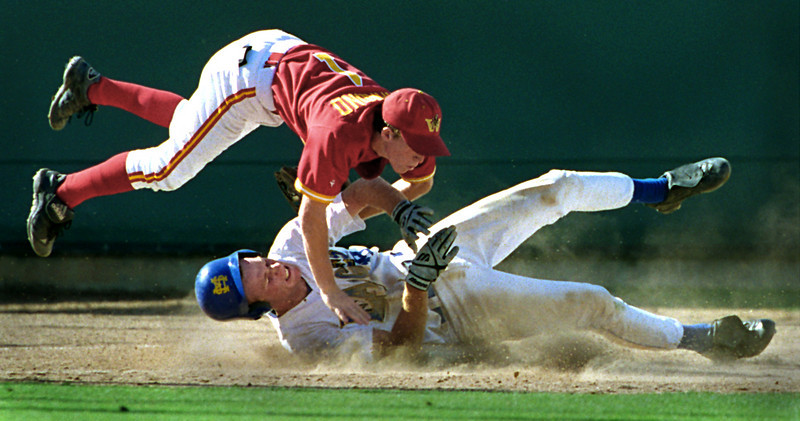 Woodbridge high school's, Jeff Hammond fly's over the top of Santa Margarita High School's, Randall Shelley as they both collide on third base. Shelley was thrown out on the play after trying to steal third.