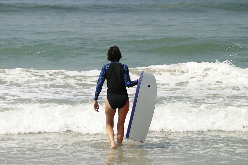 A woman in a swimsuit walking into the surf with a boogie board. This was taken from a beach near Puerto Vallarta in Mexico.